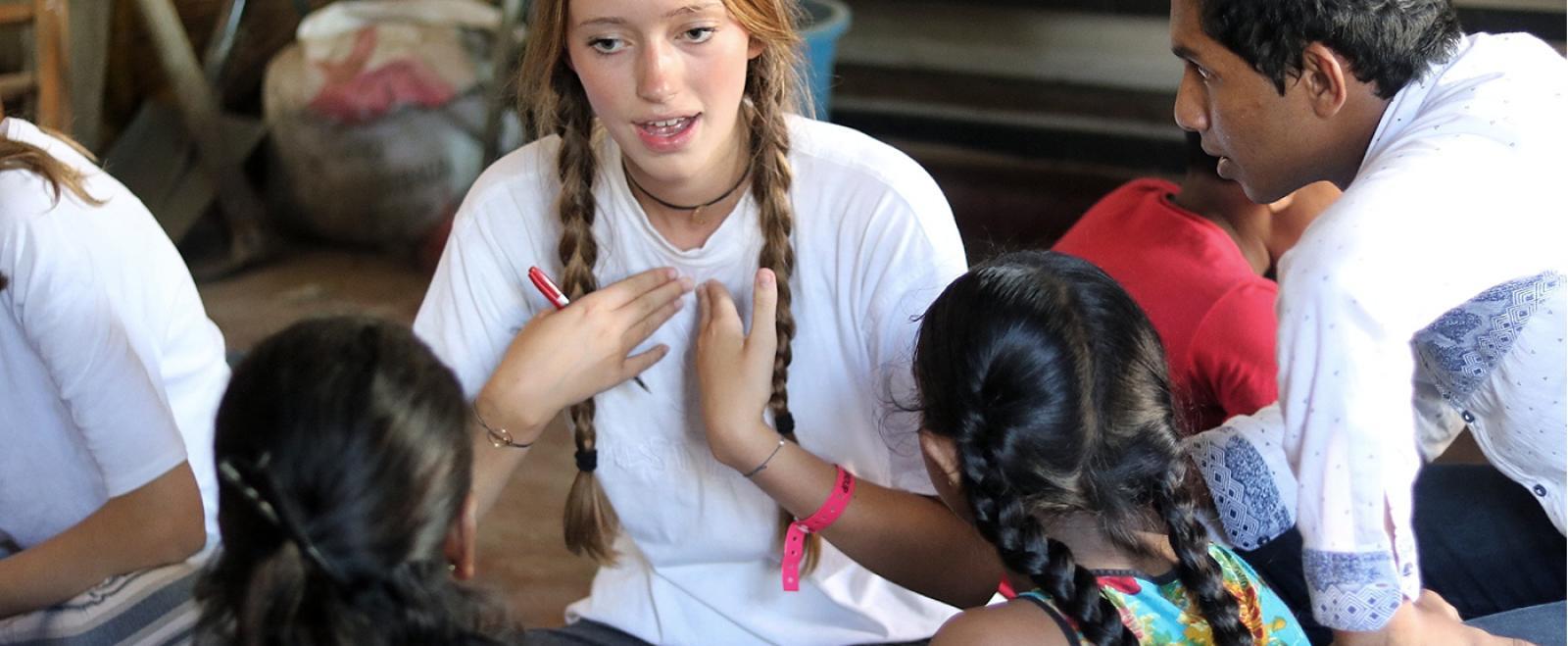 En volontär som jobbar på vårt ungdomsprojekt lär elever i Sri Lanka hur man uttalar engelska ord.